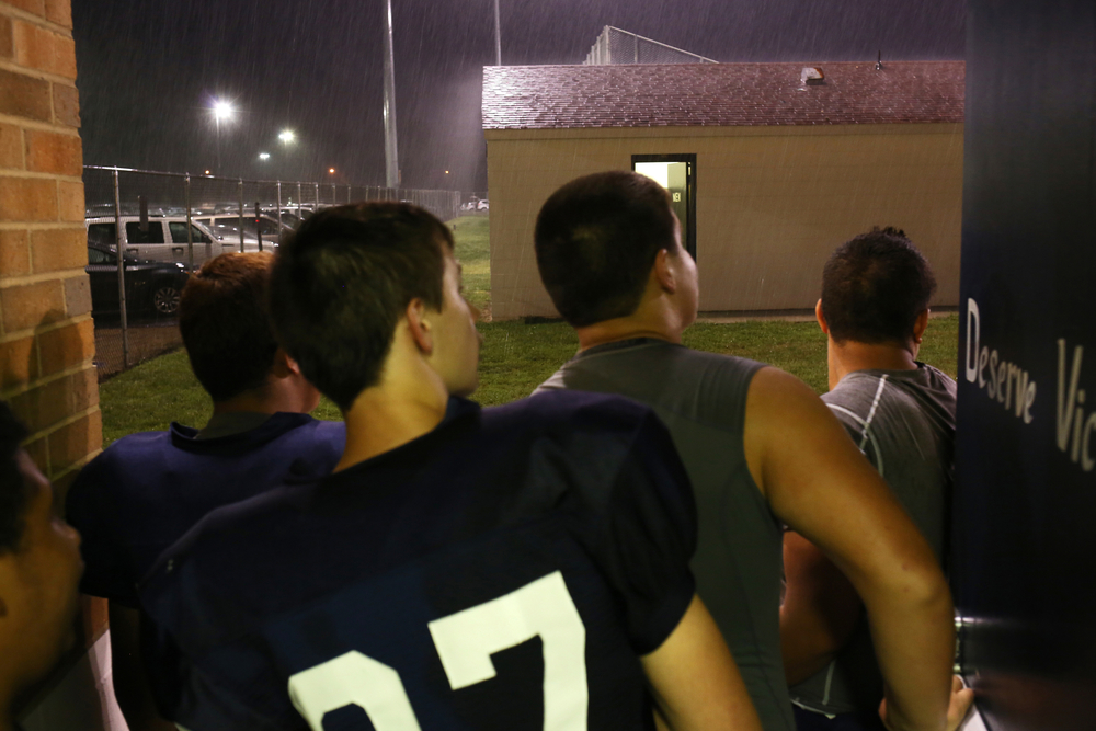 Elkhart Central football players peak their heads outside to check the weather an hour after their game against Penn got delayed due to lightning on Friday, Sept. 5, 2014, at Central. The game got postponed until Saturday.