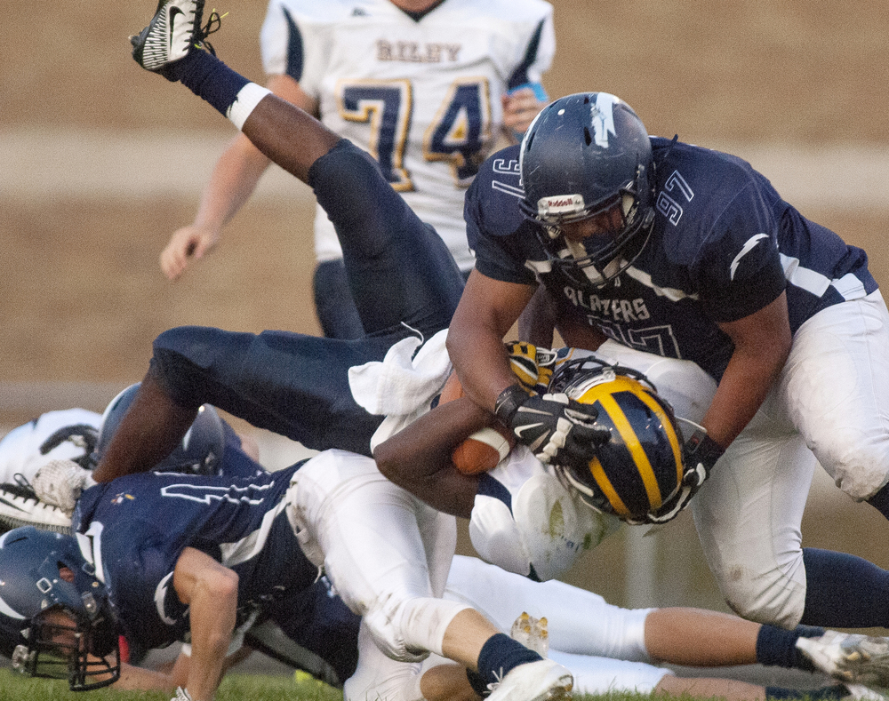 Central sophomore Devin Jones (97), top, helps bring down Riley senior Reggie Edmerson (20) in the first quarter on Friday, Sept. 19, 2014, at Rice Field.