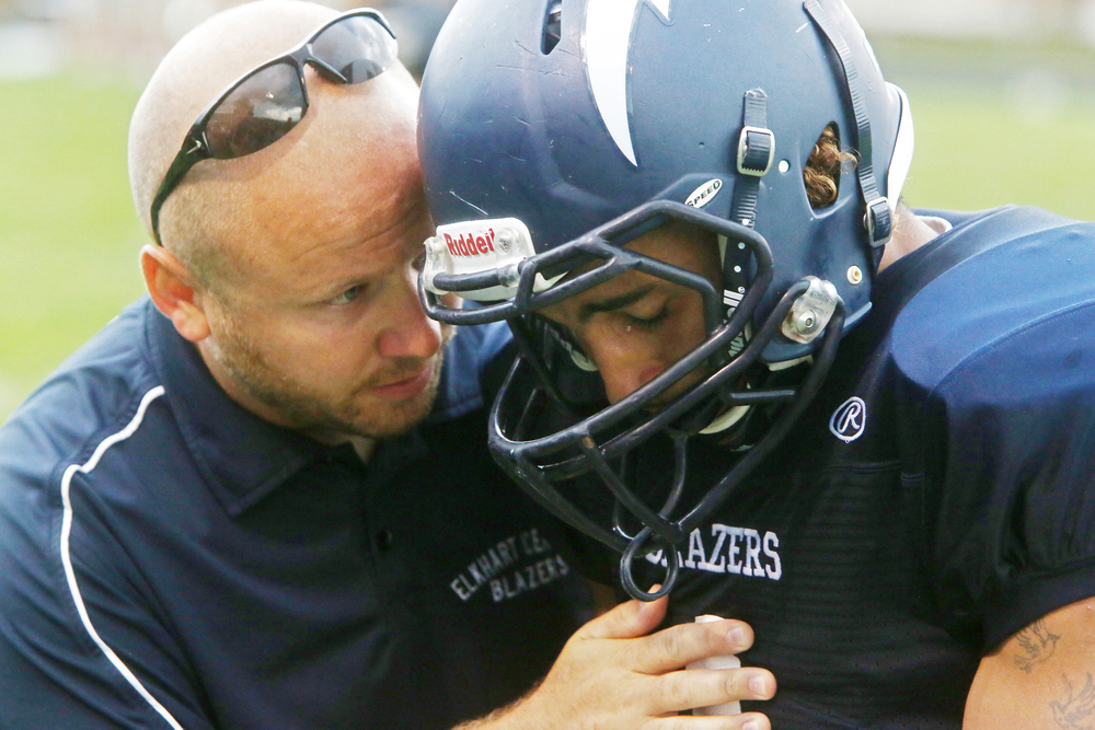 Elkhart Central coach Jeremy Hren talks with senior Joe Phillips before taking on Penn on Friday, Sept. 5, 2014, at Central. Due to a lightning delay, the game will restart at Saturday.