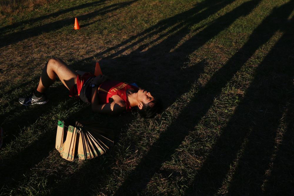 Memorial junior Steven Mittadam lays on the ground after finishing a cross country race against Memorial on Tuesday, Sept. 23, 2014, at Bonneyville Mill Park.