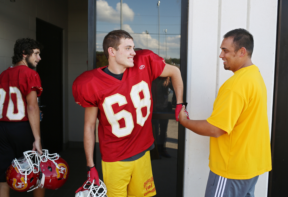 Memorial senior Dustin Ellsworth, 17, gives a strong extended handshake to offensive line coach Dan Loth after practice on Thursday, Sept. 19, 2014, at Memorial. Dustin, who has autism, started his football career with the Crimson Chargers as a student manager his freshman year and has played on the team for the last three.