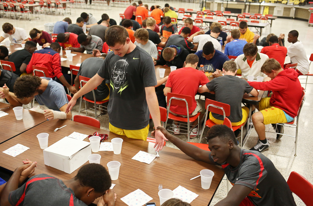 Memorial senior Dustin Ellsworth leads prayer before digging into a pasta dinner with his teammates, a night before a football game, on Thursday, Sept. 18, 2014, in Memorial.