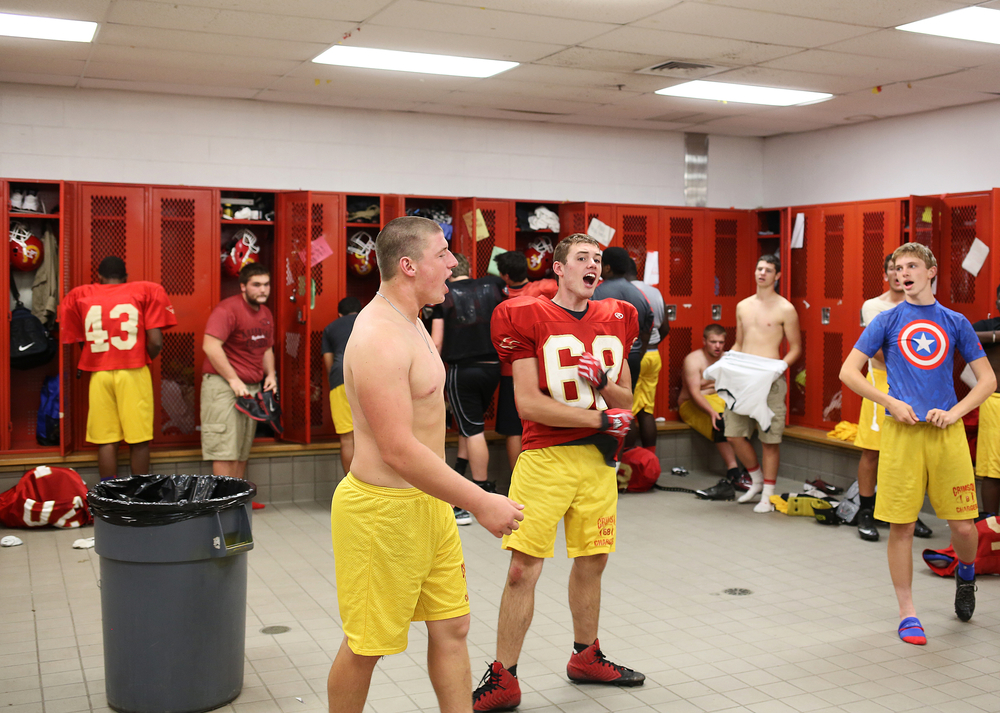 """Memorial senior Dustin Ellsworth, center in red, energetically sings """"Charge Your Fight"""" song with his teammates, as he paces the locker room at the end of practice on Thursday, Sept. 18, 2014, at Memorial."""