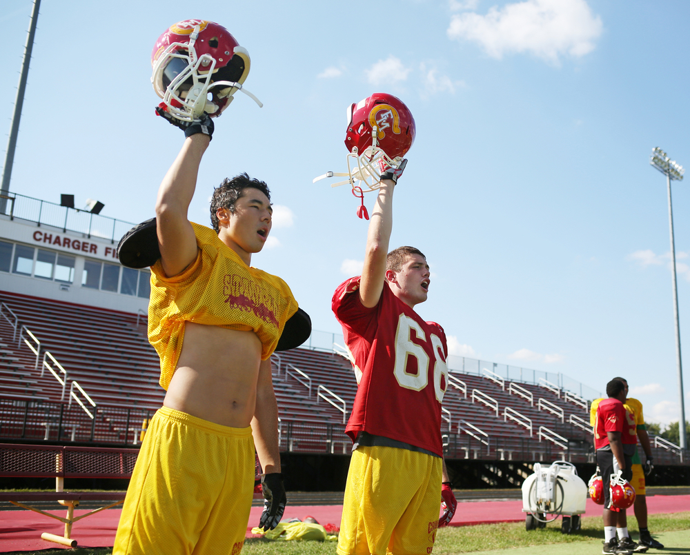 """Memorial senior Dustin Ellsworth, right, and senior Eric Holt raise their helmets during a kickoff drill at practice on Thursday, Sept. 2014, at Memorial. Holt said Ellsworth is the heart of the team. """"Through out the years, he's picked us up when we're down and whenever he's down, we pick him up,"""" Holt said."""" Without him on the team, it wouldn't Elkhart Memorial football."""""""