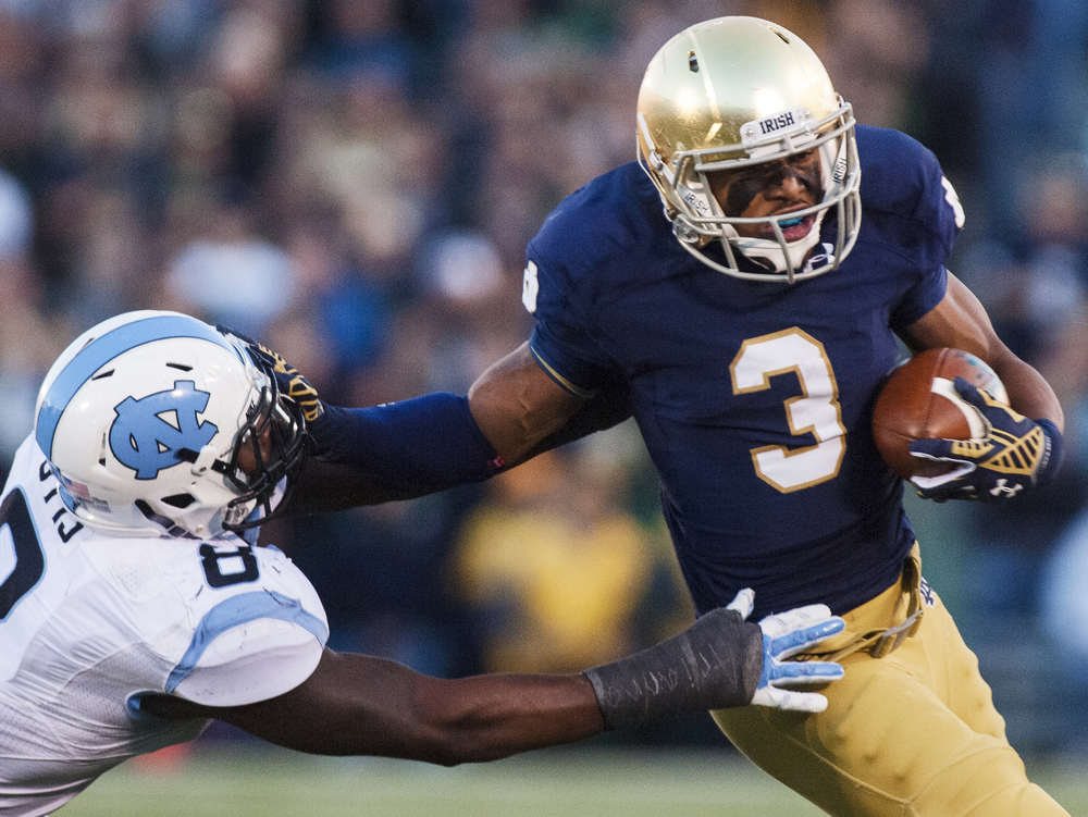 Notre Dame's Amir Carlisle (3) stiff arms North Carolina's T.J. Logan (8) in the fourth quarter on Saturday, Oct. 11, 2014, at Notre Dame Stadium in South Bend. The Fighting Irish beat the Tar Heels 50-43.