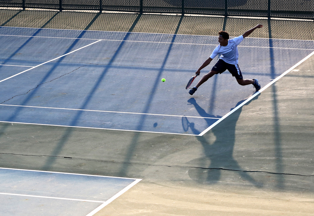 Central number three singles player, junior Curtis Hill, rallies with Concord junior Mitchell Boyer, not pictured, on Wednesday, Oct. 1, 2014, at Concord in Elkhart. Boyer won the match.