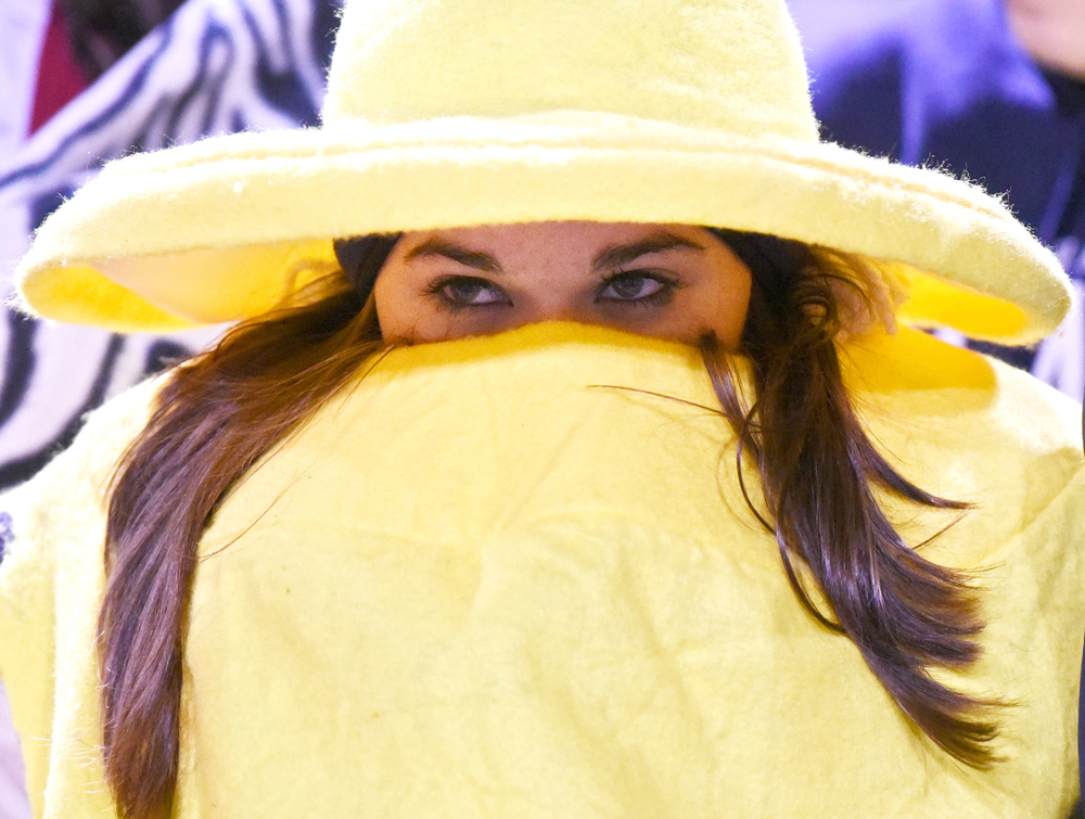 Central senior Catherine Brown hides in her mustard Halloween costume to stay warm while the Blue Blazers take on Goshen in a 5A sectional football game on Friday, Oct. 31, 2014, at Rice Field in Elkhart.