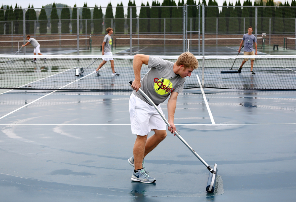 Goshen junior Hudson Kay (center) squeegees off a tennis court with junior Evan Beck, (left) senior Zach Ganger (center left) and sophomore Jacob Grewe (right) during a rained-out day of boys tennis sectionals on Thursday, Oct. 2, 2014, at Goshen Middle School.