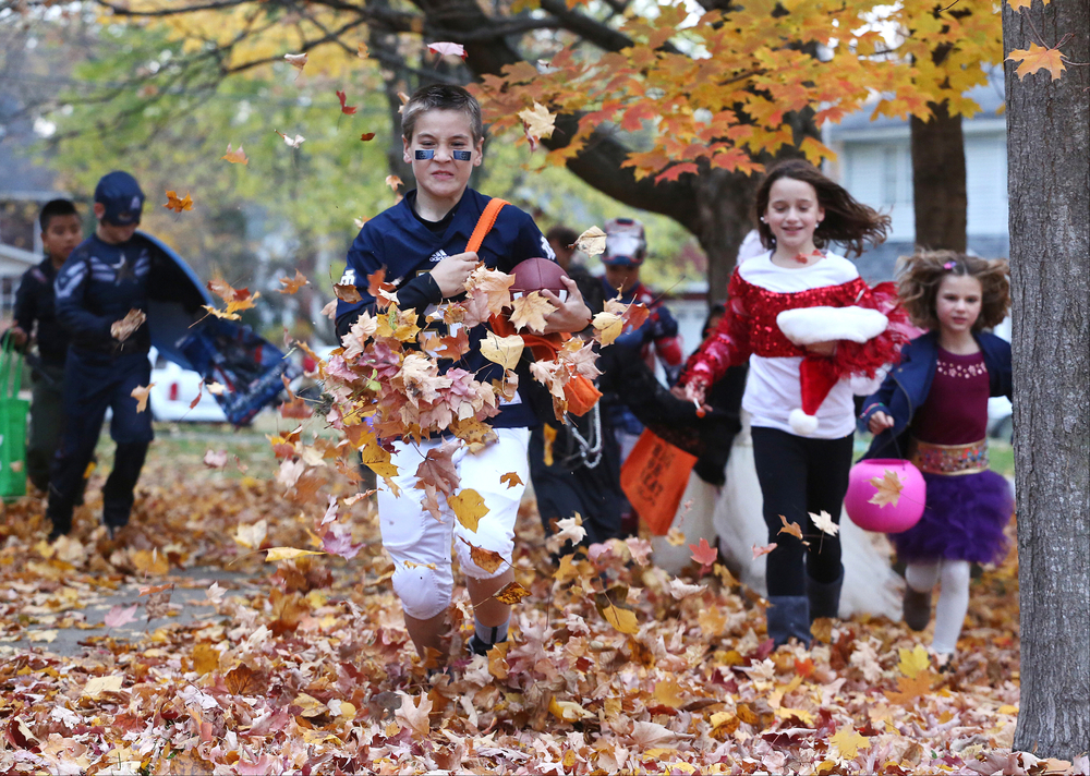 Ethan Evers, 10, dressed at Notre Dame quarterback Everett Golson kicks up leaves as he runs down the street in a search of the next house to trick-or-treat at on Thursday, Oct. 30, 2014, in Wakarusa.