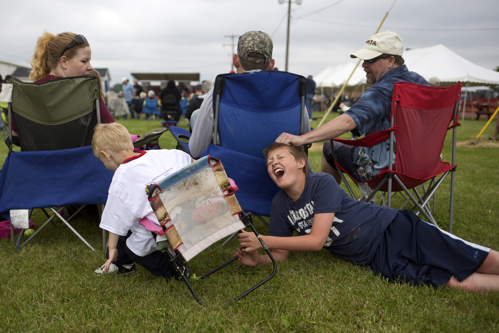 Austin Lefere playfully pulls his 13-year-old grandson Jalen Reeser's hair as he was rocking the chair his 3-year-old brother Zavien Lefere was sitting in at the 14th annual Jackson Blues Festival on Friday, June 5, 2015, at the Jackson County Airport in Jackson. Hundreds came on the second of the three-day festival out to enjoy blues music under a cloudy skies. (Nick Gonzales | Mlive.com)