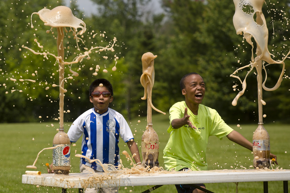 "Fourth graders Eli Stutz, 10, left, and Michael Griffin, 10, react to the explosion of Mentos and diet soda during a science experiment day Tuesday, June, 9, 2015, at Paragon Charter Academy in Jackson. Griffin said not to drink the soda after putting Mentos in. ""It will taste very bad,"" he said. The 68 fourth grade students spent the afternoon learning about chemical interactions, air pressure and electricity. (Nick Gonzales 