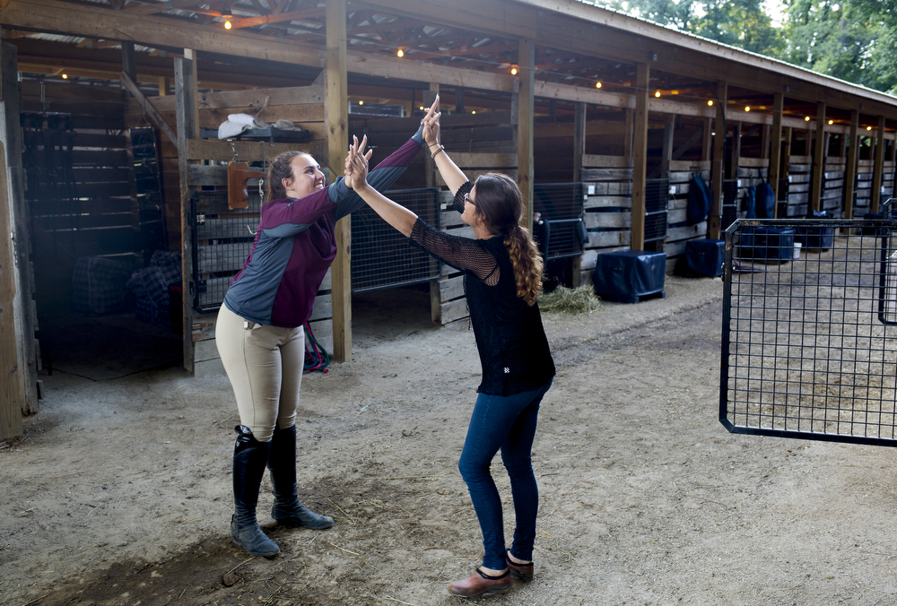 Riders Sierra King, 21, left, and Esme Gregory, 21, both of Bay City, greet each other in the stables prior taking a trip to the store Thursday evening, June 25, 2015, at Waterloo Hunt Club in Grass Lake, Michigan. The Waterloo Hunter/Jumper Classic 2 continues through Sunday. (Nick Gonzales | Mlive.com)