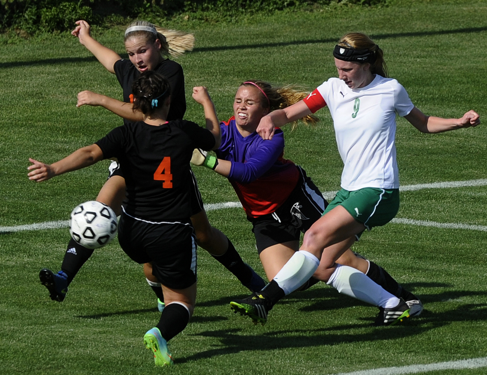 Lumen Christi's Mallory Hestwood (9) shoots past Leslie's goalkeeper Sadie Prieskorn, Sara Campbell (4) and Brooke Cowing, back, during a Division III regional semifinal girls soccer game Wednesday, June 3, 2015, in Williamston, Mich. Lumen Christi won 2-0. (Nick Gonzales | Mlive.com)