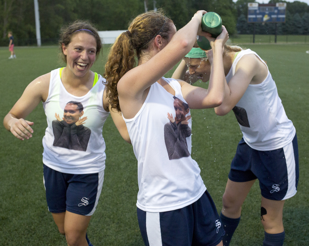Saline's Aly Dahlmann, center, squirts water at Morgan Jones next to Sofia Sweier, left, after they beat East Kentwood 1-0 in a state semifinal girls soccer game Wednesday, June 10, 2015, at Spring Arbor University.(Nick Gonzales | Mlive.com)