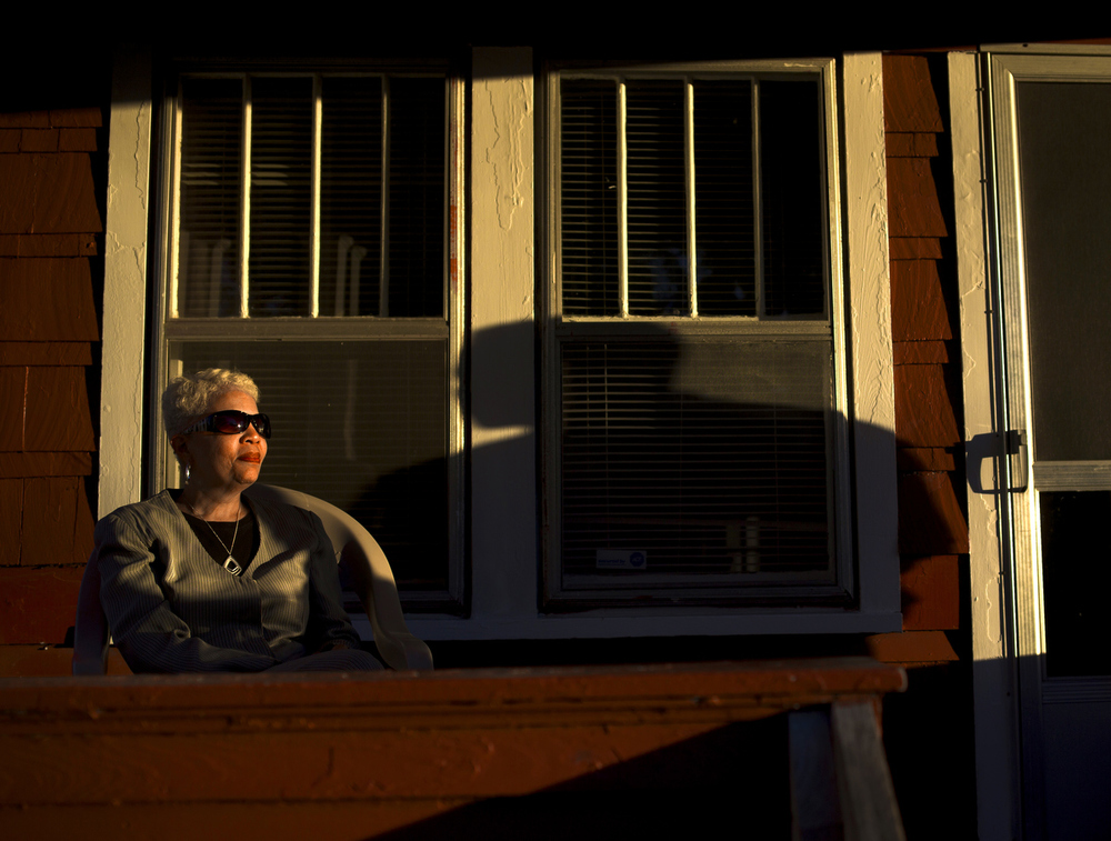 Lezlie Bowles sits on her porch bathed in afternoon light next to the shadow of Michael Grant on Wednesday, July 29, 2015, in Jackson, Mich. (Nick Gonzales | Mlive.com)