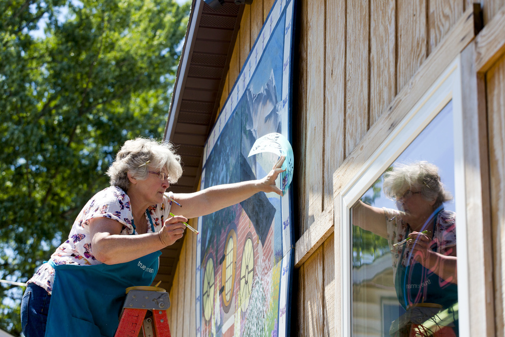 """Novajean Casler of Spring Arbor lines up her stencil on an 8-foot by 8-foot barn quilt Wednesday, July 15, 2015, at The Hobbit Place in Spring Arbor Township. Casler has been painting barn quilts for about 10 years and painting since she was a child. """"I lean toward the old, old quilt patterns,"""" she said. """"The traditional things from agriculture and our heritage. I'm not drawn to doing buildings, skyscrapers, city scenes, or anything like that. I love our heritage."""" (Nick Gonzales 