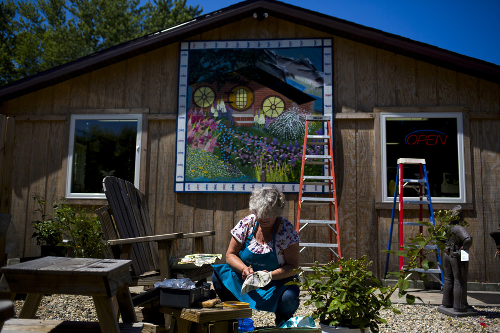 """Novajean Casler of Spring Arbor wipes paint off her paint brushes as she works on an 8-foot by 8-foot barn quilt Wednesday, July 15, 2015, at The Hobbit Place in Spring Arbor Township. Casler has been painting barn quilts for about 10 years and painting since she was a child. """"I lean toward the old, old quilt patterns,"""" she said. """"The traditional things from agriculture and our heritage. I'm not drawn to doing buildings, skyscrapers, city scenes, or anything like that. I love our heritage."""" (Nick Gonzales 