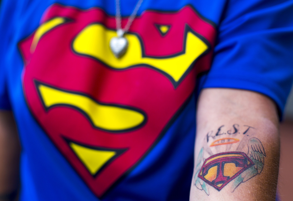 """Jackson resident Kelly Blevin shows her tattoo, which she got in remembrance of her late husband Terry Blevins on Friday, July 31, 2015, at Commonwealth Commerce Center in Jackson, Mich. Kelly said she and her family referred to her Terry as Superman. Kelly and her daughter Jordan Blevin, 23, have nearly identical tattoos and said another daughter Morgan Blevin, 16, will getting be one soon, as well. """"R.E.S.T."""" stands for """"rest easy Superman Terry,"""" and 183 means """"I love you."""" (Nick Gonzales 