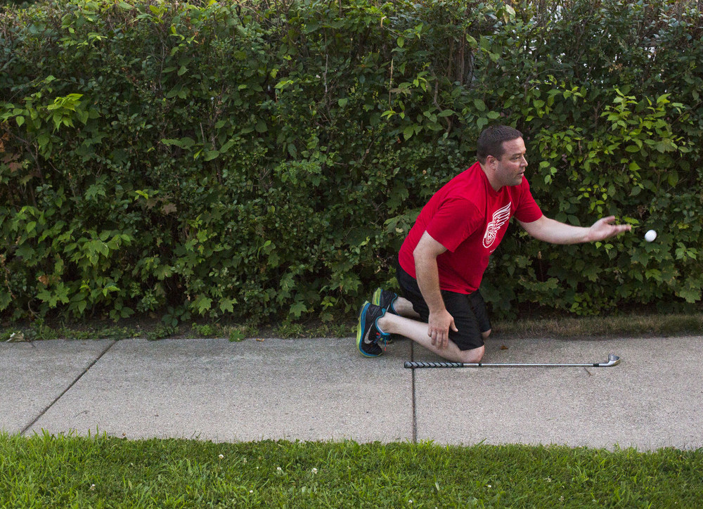 """Jamie Rippee fetches a ball from the bushes across the street from his house Tuesday, July 28, 2015, in Jackson, Mich. His 8-year-old son Kaiden Rippee started playing golf this summer and he said he thought it would be a good way to bond with him. """"It's a nice calm way to end the night,"""" he said. (Nick Gonzales 
