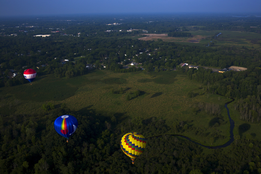 Colorful hot air balloons float in the sky during a media flight previewing the 33rd annual Hot Air Jubilee on Thursday, July 9, 2015, in Jackson, Michigan. The jubilee will take place July 17-19 at Ella Sharp Park. (Nick Gonzales | Mlive.com)