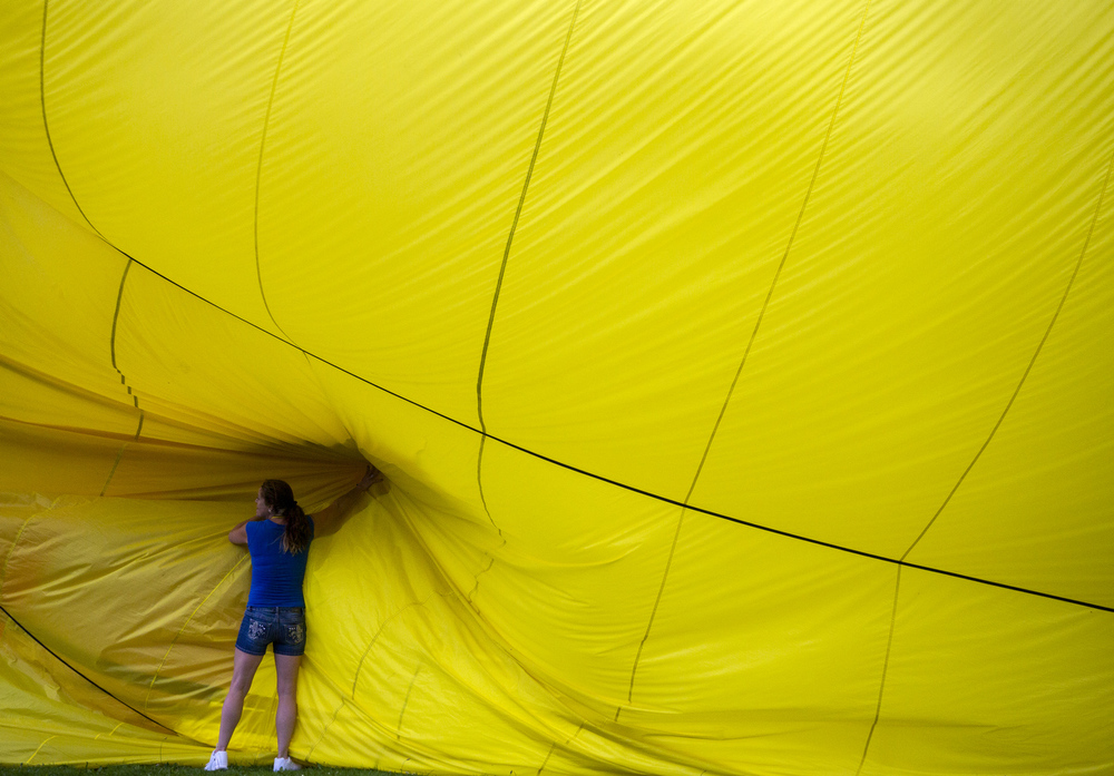 A woman helps to pack up hot air balloon Double Yellow after drying it out at the Hot Air Jubilee on Saturday, July 18, 2015, at Ella Sharp Park in Jackson, Michigan. A tornado watch barred evening hot air balloon launches and the night glow. The jubilee will conclude with an early morning launch Sunday. (Nick Gonzales | Mlive.com)