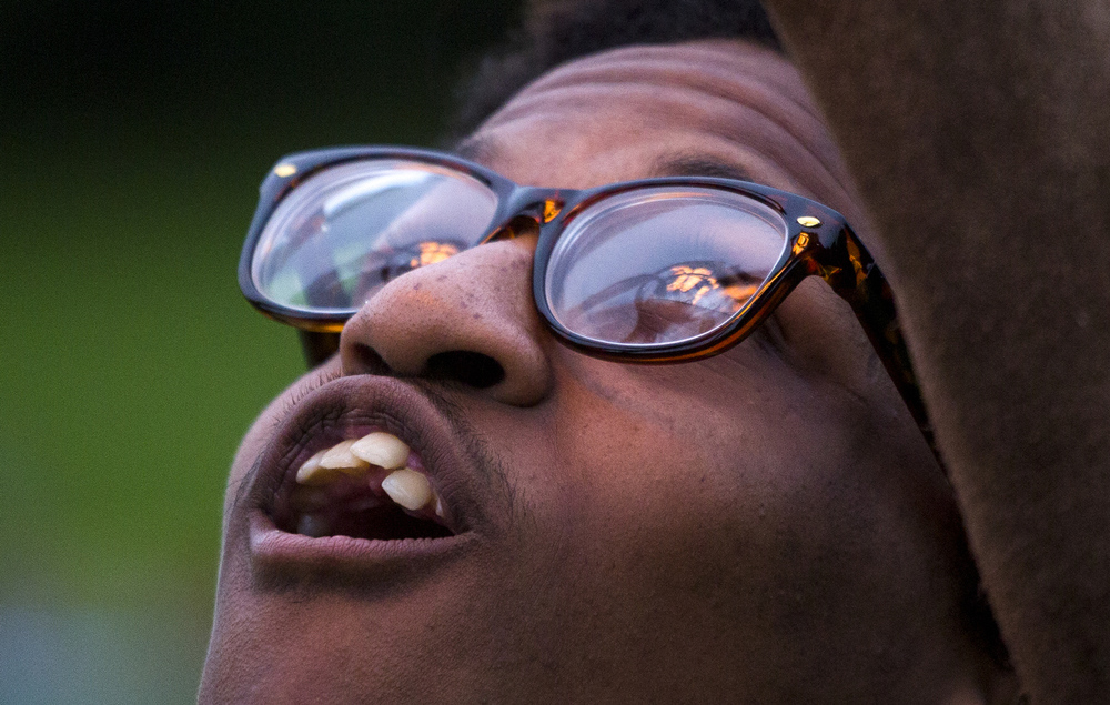 Jackson resident D'Angelo Brown, 19, reacts to seeing flames shoot from a hot air balloon burner at the Hot Air Jubilee on Saturday, July 18, 2015, at Ella Sharp Park in Jackson, Michigan. Brown said he's interested in hot air balloons but is scared of heights. A tornado watch barred evening hot air balloon launches and the night glow. The jubilee will conclude with an early morning launch Sunday. (Nick Gonzales | Mlive.com)
