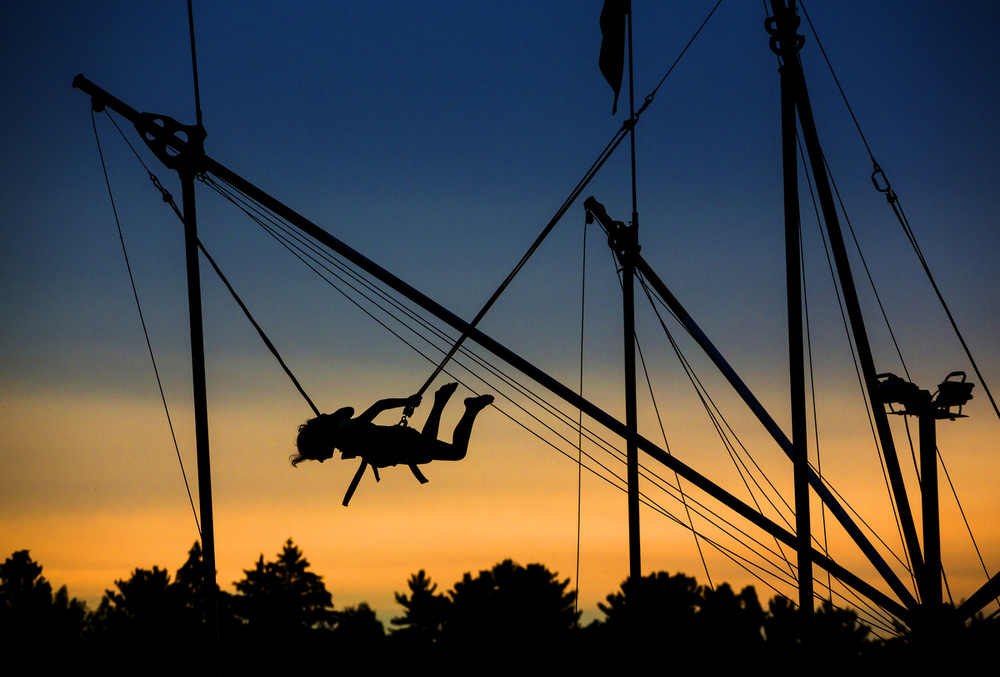 A girl bounces in the air with the help of bungee cords at the Hot Air Jubilee on Saturday, July 18, 2015, at Ella Sharp Park in Jackson, Michigan. A tornado watch barred evening hot air balloon launches and the night glow. The jubilee will conclude with an early morning launch Sunday. (Nick Gonzales | Mlive.com)