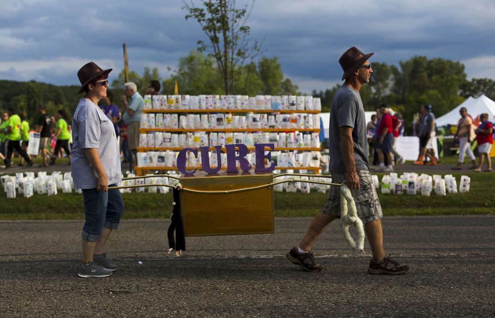 "Two people carry a box with ""cure"" written on it at Relay for Life on Friday, Aug. 7, 2015, at Cascade Falls Park in Jackson, Mich. Thousands came out to support people fighting cancer and remember those who lost their lives to cancer.  (Nick Gonzales 
