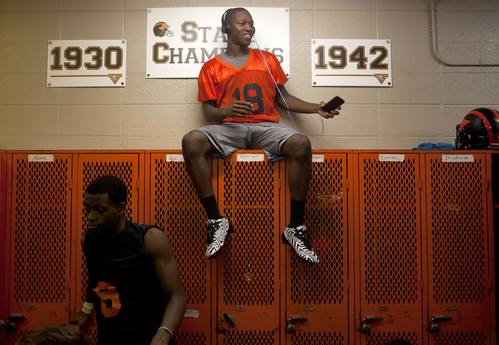 Senior Daniel Gant listens to music on top of lockers during a brief weather delay in the Vikings' first day of football practice Monday, Aug. 10, 2015, at Jackson High School. (Nick Gonzales | Mlive.com)