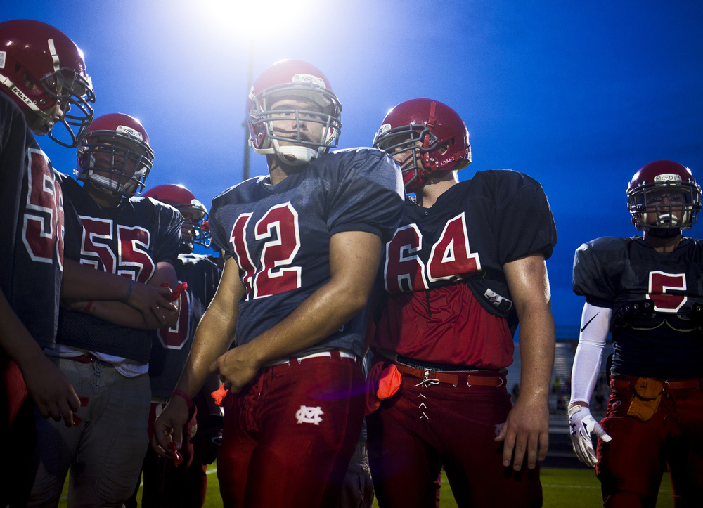 Michigan Center senior quarterback Tavian Gaddy, center, huddles with teammates between drills during a football practice in front of parents and fans Wednesday, Aug. 19, 2015, at Michigan Center High School. (Nick Gonzales | Mlive.com)