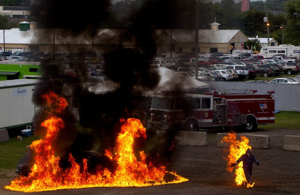 A man on fire runs from a burning car during a stunt at a monster truck show Friday, Aug. 14, 2015, at the Jackson County Fair in Jackson, Mich. The fair continues Saturday. (Nick Gonzales | Mlive.com)