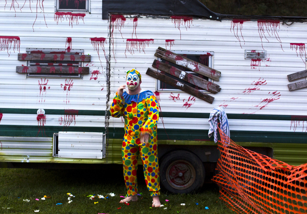 A clown dodges water gallons next to a haunted trailed at Relay for Life on Friday, Aug. 7, 2015, at Cascade Falls Park in Jackson, Mich. (Nick Gonzales | Mlive.com)