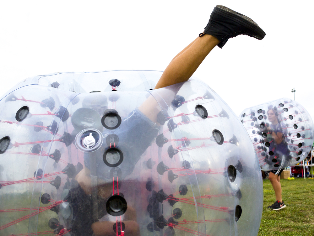 Adrian residents Alex Kelly, 14, rolls upsides down near McKenna Young, 13, as they play bubble soccer at the Big Mitten Fair on Friday, Sept. 4, 2015, at Michigan International Speedway in Brooklyn, Mich. The fair continues through Monday, Sept. 7. (Nick Gonzales | Mlive.com)