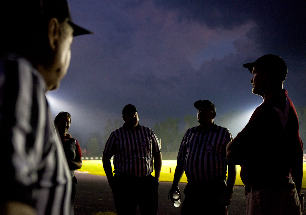 Michigan Center's head coach Troy Allen, right, discusses the weather delay with referees during a football game between Michigan Center and Hanover-Horton on Thursday, Sept. 3, 2015, at Hanover-Horton High School. (Nick Gonzales | Mlive.com)