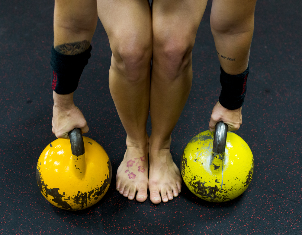 """Jackson resident Jenny Terry, 34, prepares to lift two kettlebells during a workout Saturday, Sept. 5, 2015, at Kettlebell Hot Spot in Spring Arbor, Mich. Four members of the training center will compete in the kettlebell world championships come November in Dublin, Ireland. Terry said she's never found a workout that fits her until she tried kettlebell. """"I think I could have been a better athlete in my 20s."""" she said """"I'm definitely in the best shape of my life."""" (Nick Gonzales 