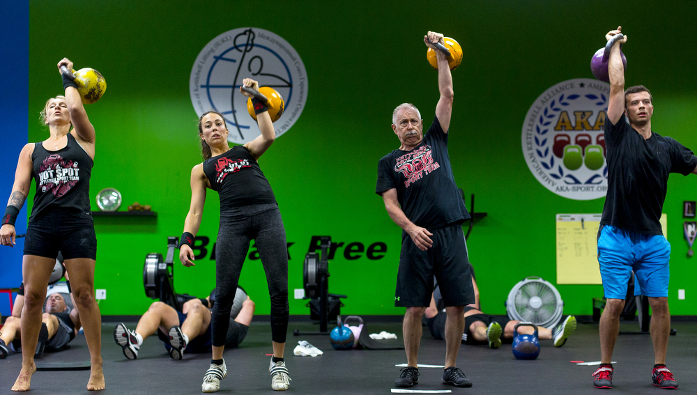 Jenny Terry, 34, from left, Kelsie Minder, 24, Richard Morton, 61, and Chris Seward, 23, jerk – a basic lift of the kettlebell above the head – during a workout Saturday, Sept. 5, 2015, at Kettlebell Hot Spot in Spring Arbor, Mich. The four members of the training center will compete in the kettlebell world championships come November in Dublin, Ireland. (Nick Gonzales   Mlive.com)