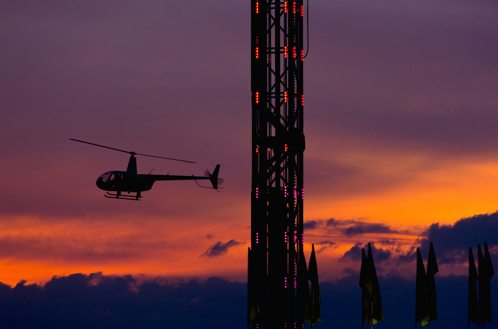 People take a helicopter ride in front of the sunset at the Big Mitten Fair on Friday, Sept. 4, 2015, at Michigan International Speedway in Brooklyn, Mich. The fair continues through Monday, Sept. 7. (Nick Gonzales | Mlive.com)
