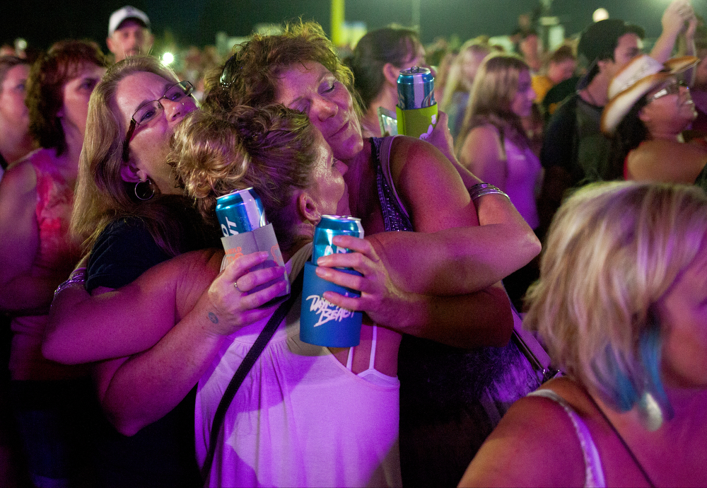 Women hug during John Michael Montgomery's performance at the Big Mitten Fair on Monday, Sept. 7, 2015, at Michigan International Speedway in Brooklyn, Mich. The fair concluded with a concert featuring John Michael Montgomery and Chris Janson. (Nick Gonzales | Mlive.com)