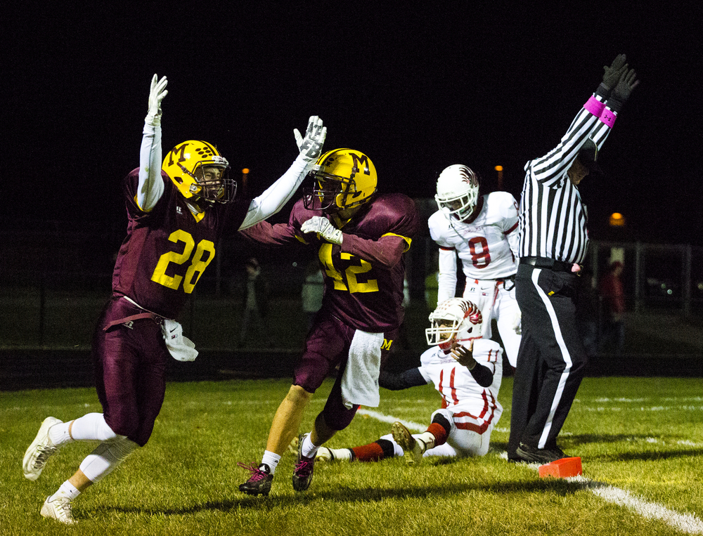 Manchester's Jordan Good (28), left, and Caleb Goodell (42) celebrate's Good's touchdown near Vandercook Lake's Noah Cooper (11) and Chase Pierce (8) during a football game between Manchester and Vandercook Lake on Friday, Oct. 16, 2015, at Manchester High School. Manchester won 29-7 and wins the Cascades title. (Nick Gonzales | Mlive.com)