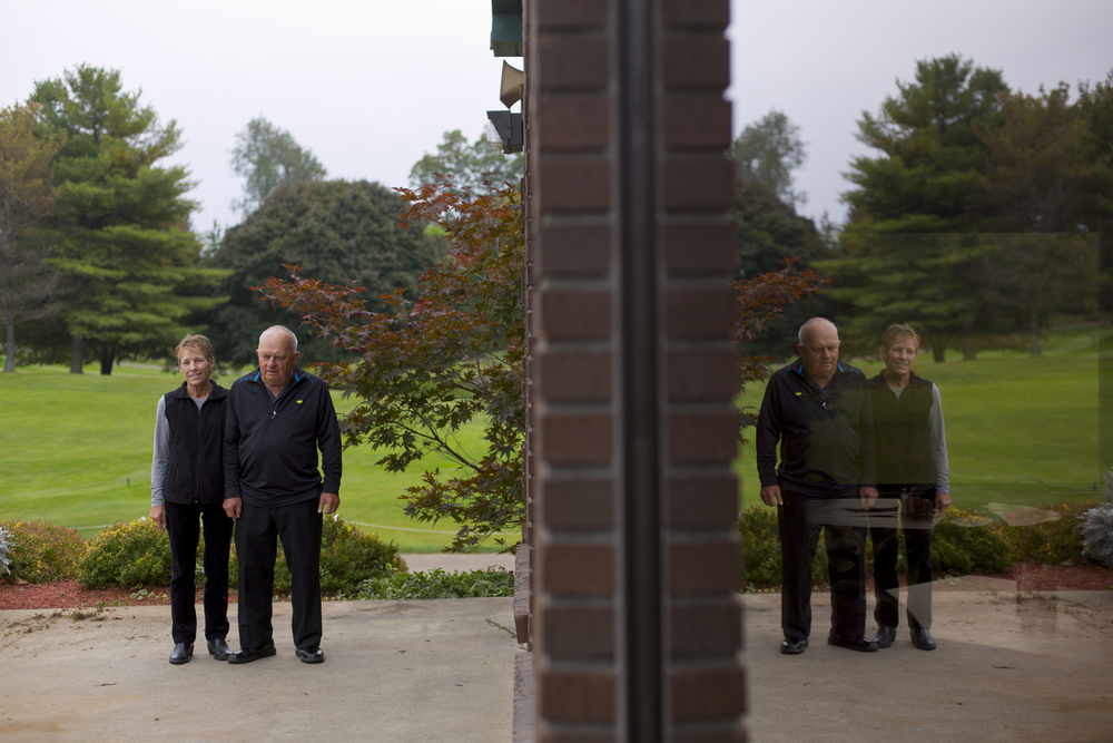 """Jeanne and her husband David """"Inch"""" Kasprzycki stand near the clubhouse and are reflected in a window at Hankerd Hills Golf Course on Tuesday, Oct. 6, 2015, in Pleasant Lake, Mich. They have owned the golf course for 37 years. (Nick Gonzales 