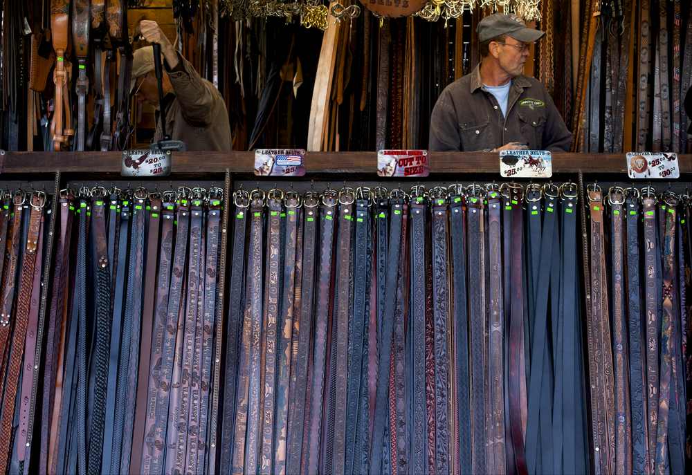 People work surrounded by leather belts at the Hillsdale County Fair on Thursday, Oct. 1, 2015, in Hillsdale, Mich. The fair continues through Saturday, Oct. 3. (Nick Gonzales | Mlive.com)