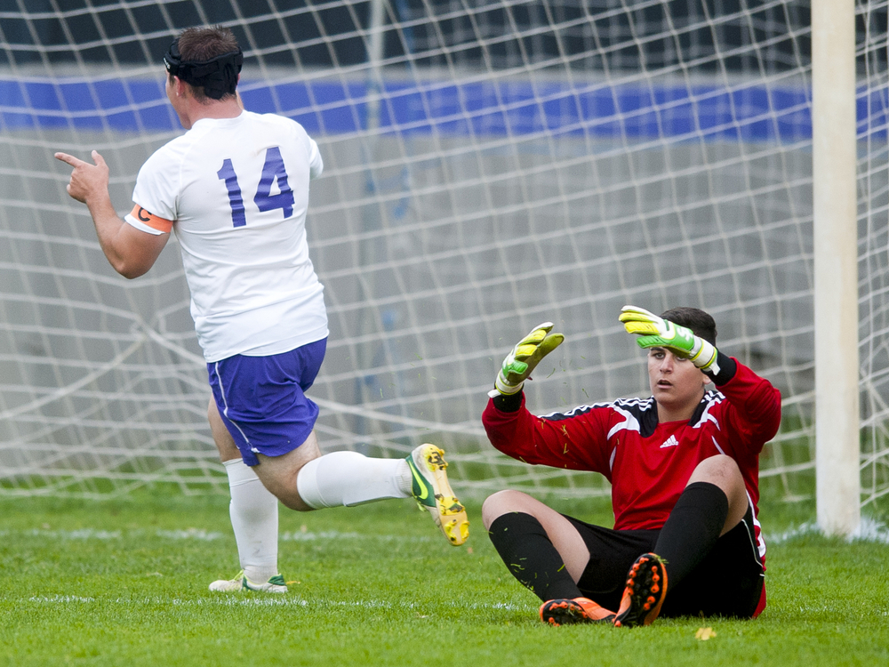 Quincy's goalkeeper Edwardo Bryan reacts as Jackson Christian's John McNeil (14) celebrates scoring a game-ending goal during a boys soccer game Monday, Oct. 12, 2015, at Jackson Christian High School in Jackson, Mich. Jackson Christian won 8-0 with a mercy rule victory. (Nick Gonzales | Mlive.com)