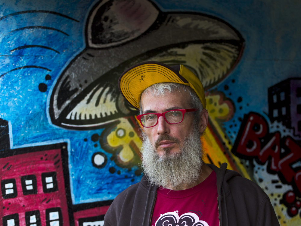 Artist Thor Goodlife, 43, stands near a painting in his backyard Monday, Oct. 12, 2015, that his children helped him paint at his Hillsdale County, Mich., home. Goodlife recently painted a mural under the Mechanic Street bridge. (Nick Gonzales | Mlive.com)