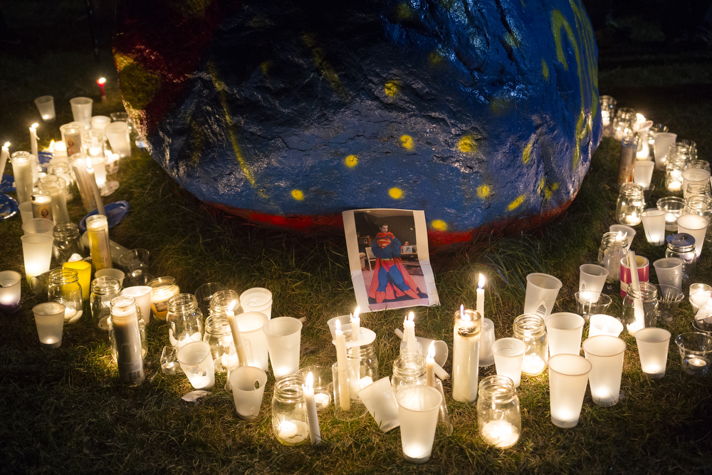 A picture of Logan Bailey dressed in a Superman costume is surrounded by candles at a candlelight vigil for him Sunday, Nov. 1, 2015, at Vandercook Lake High School in Vandercook Lake, Mich. Bailey passed away the day before, Saturday, Oct. 31. Hundreds gathered to remember and pay respects to Bailey's family. (Nick Gonzales | Mlive.com)