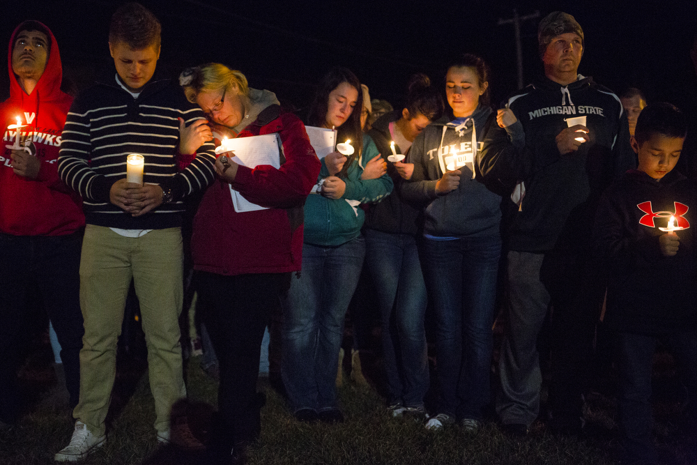 Christal Hamlin, in red, hangs onto her 15-year-old Nicolas' arm at a candlelight vigil for Logan Bailey, 15,  on Sunday, Nov. 1, 2015, at Vandercook Lake High School in Vandercook Lake, Mich. Bailey passed away Saturday, Oct. 31. Hundreds gathered to remember and pay respects to Bailey's family. (Nick Gonzales | Mlive.com)