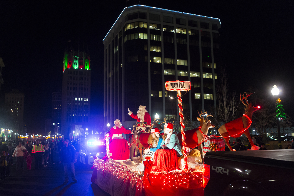 """Mr. and Mrs. Claus waves during the 25th annual Christmas parade Friday, Nov. 20, 2015, on Michigan Avenue in downtown Jackson, Mich. """"Silver bells Christmas"""" was this year's theme, which featured floats, clowns, marching bands and ended with Santa. (Nick Gonzales 