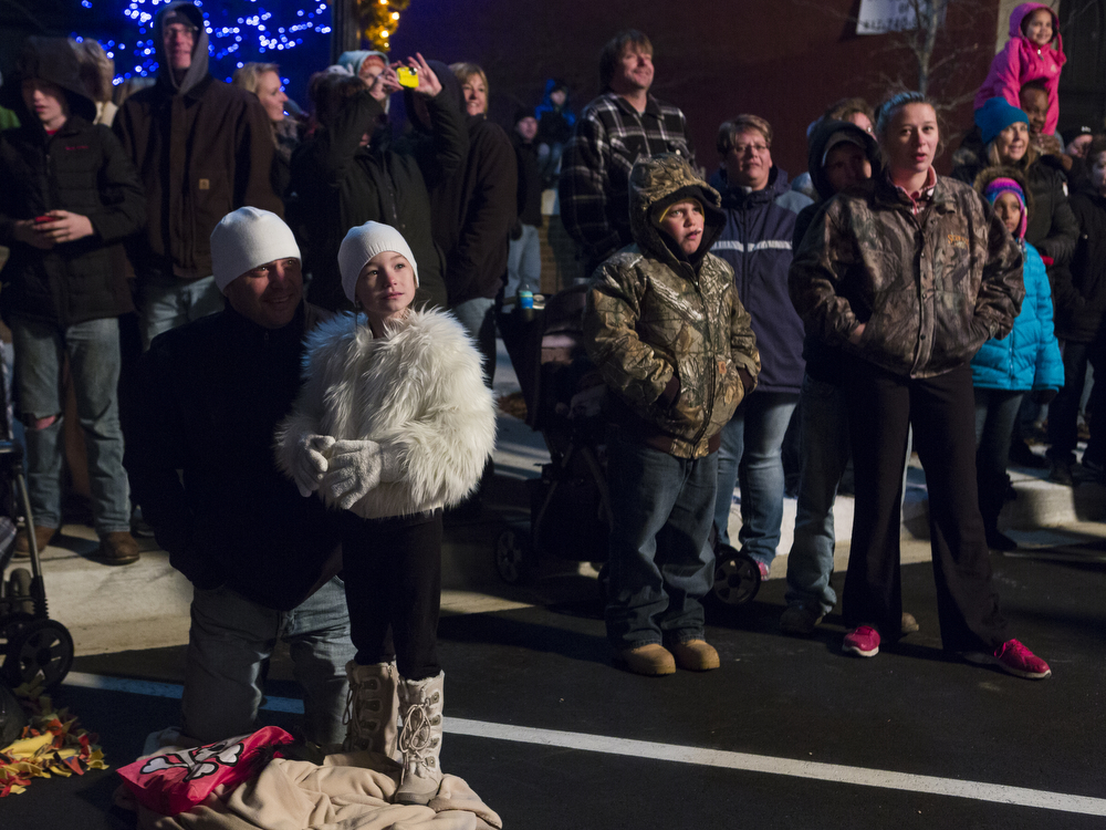 """People watch floats go by during the 25th annual Christmas parade Friday, Nov. 20, 2015, on Michigan Avenue in downtown Jackson, Mich. """"Silver bells Christmas"""" was this year's theme, which featured floats, clowns, marching bands and ended with Santa. (Nick Gonzales 