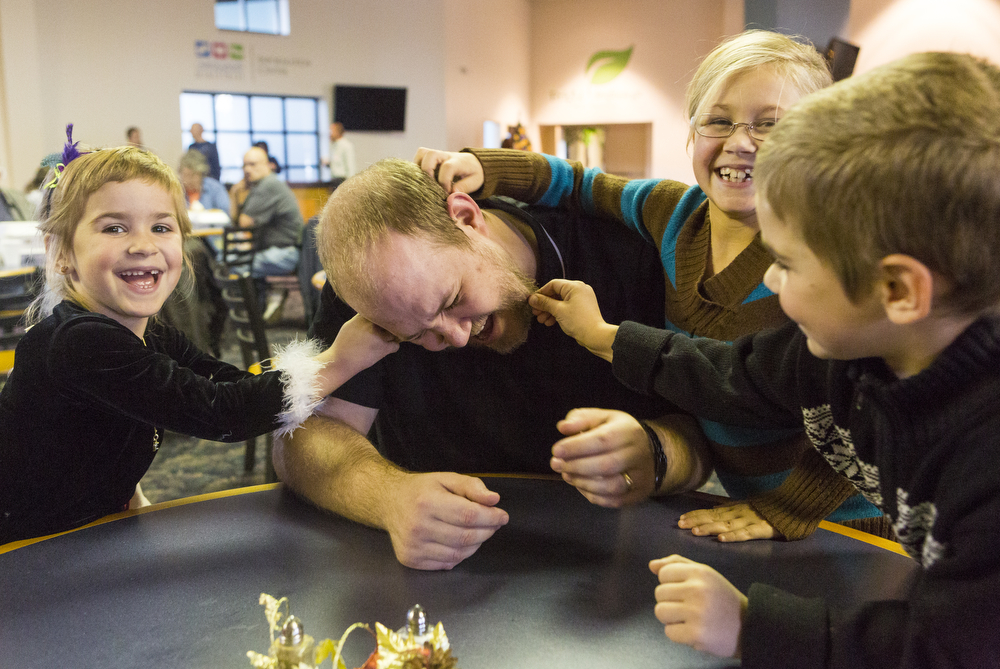 Robert Bushong's children Arianna, 5, from left to right, Olivia, 8, and Andrew, 7, pull at his hair at a free community Thanksgiving day meal Thursday, Nov. 26, 2015, at the Church of the Nazarene in Blackman Township, Mich.  Compassionate Ministries of Jackson County organized the event and served hundreds. (Nick Gonzales | Mlive.com)