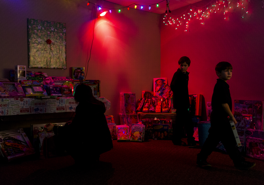 """Andrew Keppler, 8, center, and his brother James Keppler,6, right, pick out a toy at the Walton Insurance Group 12th annual Christmas walk through Thursday, Dec. 3, 2015, at Walton Insurance Group in Jackson, Mich. The office was turned into a Christmas wonderland with Mr. and Mrs. Claus, reindeer outside, caroling and a free gift at the end of the maze. The event was named the """"12 years of Christmas."""" (Nick Gonzales 