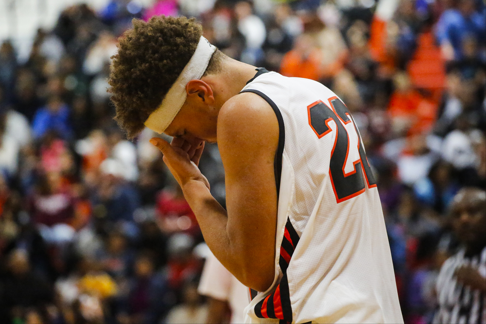Jackson's Karinn Davis (22) holds his head after hitting the ground hard during a boys basketball game Friday, Dec. 11, 2015, at Jackson High School in Jackson, Mich. East Lansing beat Jackson, 53-49. (Nick Gonzales | Mlive.com)